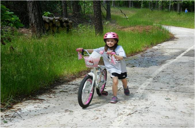 Little girl pushing bike on trail